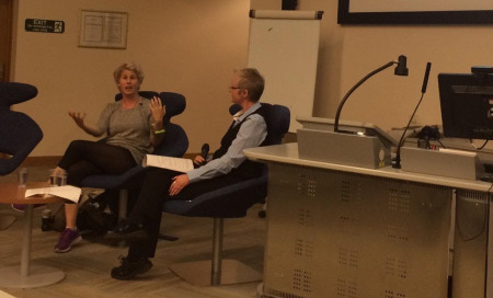 photo of Julie seated with Caroline Cridao-Perez at the front of a lecture theatre with Caroline animated and speaking