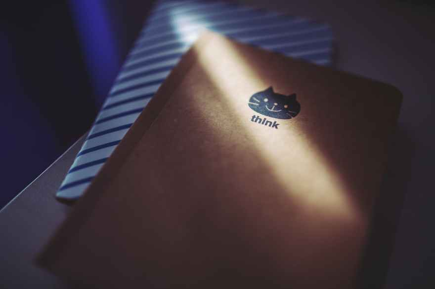 photo of a notebook with a small icon of cat's face with the word 'think' printed underneath