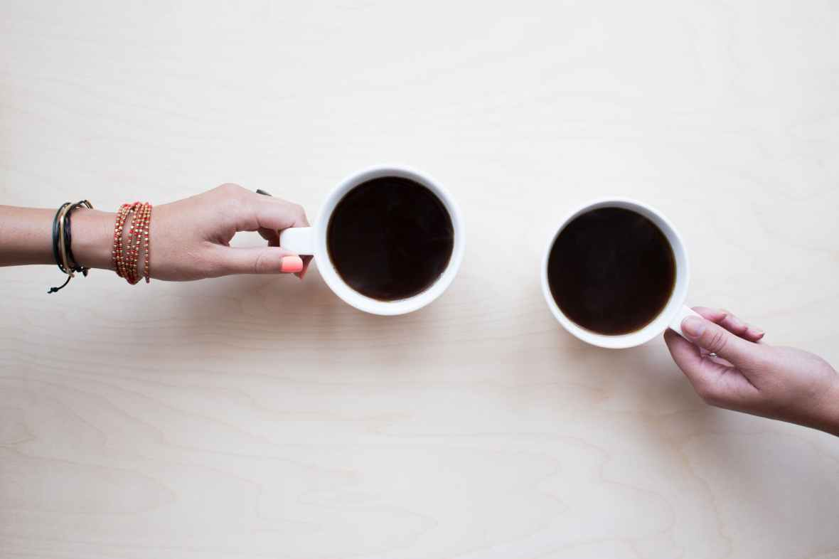 seen from above, two cups of coffee on a table, with hands of two different women visible holding the mug handles