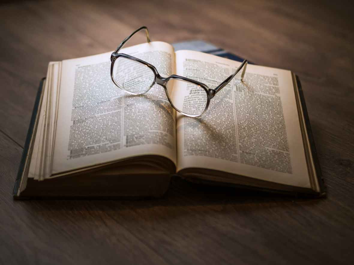 a pair of spectacles resting on an open book