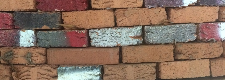bricks of different colours and sizes as if in a wall