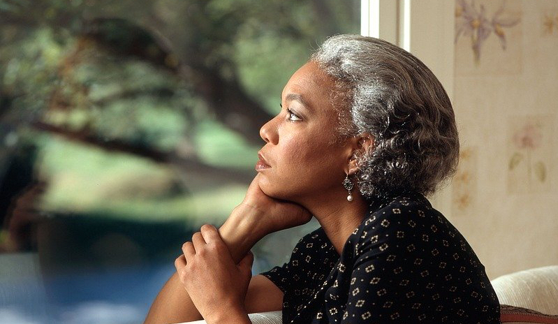 Portrait of woman looking out of a window looking pensive